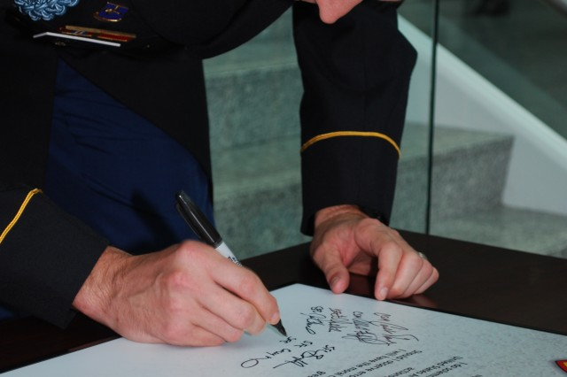 "Sgt. 1st Class Shane Machleit, Army Evaluation Center, signs the NCO Creed during a ceremony at the U.S. Army Test and Evaluation Command headquarters building Sept. 28 as part of the Army's Profession of Arms ""Operation Solemn Promise"" campaign."