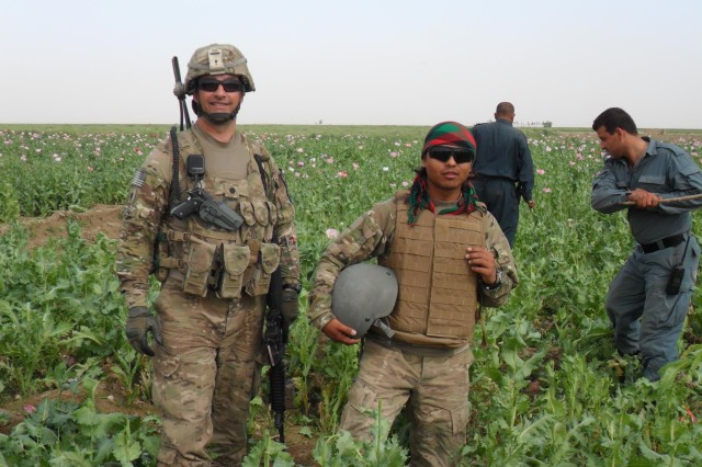 DAND, AFGHANISTAN --Angola, N.Y. resident Lt. Col. Russell Clark (left), poses with his interpreter in an opium poppy field as Afghan National Police (ANP) use sticks to hack off the plants' seed pods before they can be used to make heroin. The field is just one of many the Dand District ANP destroyed last spring under the mentorship of Clark and other New York Army National Guard Soldiers. (Photo courtesy of Lt. Col. Russell Clark, New York Army National Guard)