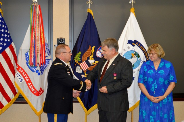 Col. James Wetzel, deputy chief of staff G-2, U.S. Army Space and Missile Defense Command/Army Forces Strategic Command, presents John Davis, intelligence specialist, with his retiree pin during his retirement at the command's Redstone Arsenal headquarters Sept. 21 while Davis' wife, Jane looks on. Davis retires with 37 years of service.