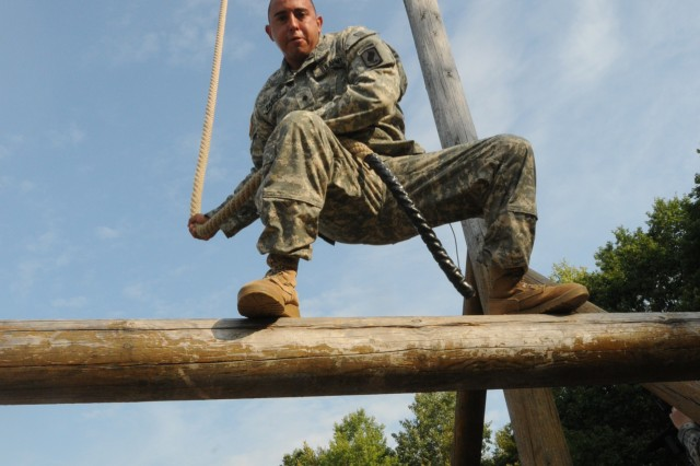 An Air Assault student swings from a rope onto a ledge, as he navigates through the obstacle course on day zero of the 21st Theater Sustainment Command-hosted Air Assault Course, which took place on Camp Robertson in Schweinfurt, Germany. (Photo by Staff Sgt. Michael J. Taylor, 21st TSC Public Affairs)