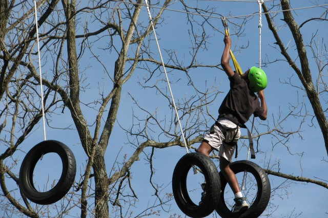 A military youth challenges himself during the rope obstacle course while attending the 200th Military Police Command's Spring Break Camp 2012.