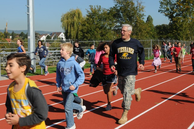 """Maj. Gen. James Boozer, deputy commander of U.S. Army Europe, runs with students on the newly constructed track at the Wiesbaden Middle School, Oct. 1, 2012. Boozer visited the students as part of Weisbaden's """"Fueling the Future"""" campaign kick-off event. The fueling program is designed to educate children and parents on the benefits of making healthier food choices and routine physical activity."""