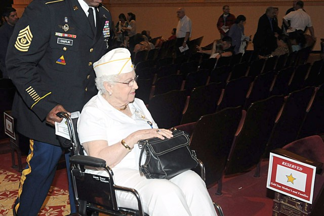 Command Sgt. Maj. Alvin Chaplin Sr., Headquarters, Headquarters Battalion, U.S. Army North, helps one of the senior Gold Star Mothers, Esther Campbell Gates, out of the theater following the Survivor Outreach Services Ribbon Cutting ceremony, Sept. 29, 2012, at the Fort Sam Houston (Texas) Theater. Gates' son, Spc. 4 Keith Campbell, was killed in action in Vietnam in February of 1967. The post library is dedicated in his name.