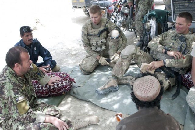 Capt. Sayed Baba Mansory (far left), officer in charge, 1st Kandak, 2nd Brigade, 205th Corps, Afghan National Army, Shamulzai district, and Afghan National Police district commander, Lt. Shah Khan, Shamulzai district commander, sit with Matthew Domenech (far right), platoon leader, 3rd Platoon, Battle Company, 5th Battalion 20th Infantry Regiment, Task Force 1st Squadron, 14th Cavalry Regiment and one of the village elders (bottom) to discuss security and welfare issues in the village of Ruzek, Afghanistan. Village concerns are often discussed in an informal setting where leaders sit and talk over many glasses of chai tea.
