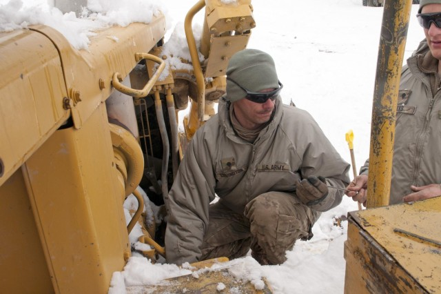 Spc. James Covington repairs the starter on a Caterpillar D8 Bulldozer at Forward Operating Base Sweeney, Afghanistan, Feb. 19, 2012. The bulldozer will clear the roads from FOB Sweeney to the villages of Menden Kheyl and Shinkai, allowing residents from the area to reach the Shinkai Bazaar.