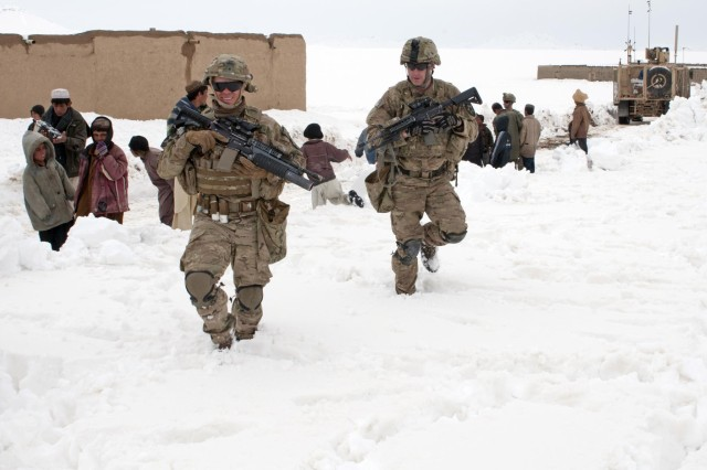 Sgt. Nick Lightwine and Sgt. Rob Logue, 5th Battalion 20th Infantry Regiment, Task Force 1st Squadron 14th Cavalry Regiment, make their way to their mine resistant ambush protected truck following a successful snow clearance patrol through the village of Menden Kheyl, Afghanistan, Feb. 19, 2012. Battle Company helped provide security for the bulldozer that cleared the roads from FOB Sweeney to the villages of Menden Kheyl and Shinkai, allowing residents from the area to reach the Shinkai bazaar.