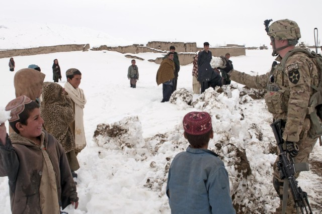 Sgt. Robert Logue, Battle Company, 5th Battalion 20th Infantry Regiment, Task Force 1st Squadron 14th Cavalry Regiment, tosses snowballs back and forth with some of the children from the village of Meden Kheyl, Feb. 19, 2012. Battle Company partnered with the Afghan National Army to help clear the roads from Forward Operating Base Sweeney to the villages of Menden Kheyl and Shinkai, following 3 days of snow, allowing residents from the area to reach the Shinkai Bazaar.