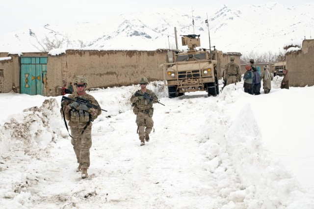Sgt. Philip Vota and Spc. Patrick Intorre, Battle Company, 5th Battalion 20th Infantry Regiment, Task Force 1st Squadron 14th Cavalry Regiment, ground guide their mine resistant ambush protected vehicle through the village of Sadu Kala, Afghanistan, Feb. 19, 2012. Battle Company partnered with the Afghan National Army to help clear the roads from Forward Operating Base Sweeney to the villages of Menden Kheyl and Shinkai following three days of snow, allowing residents from the area to reach the Shinkai Bazaar.