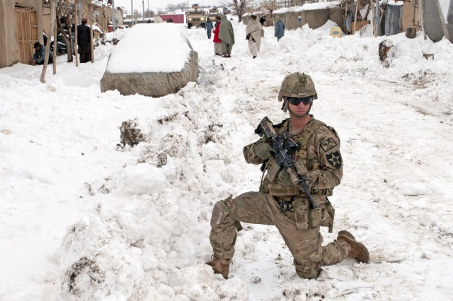 Spc. Patrick Intorre, Battle Company, 5th Battalion 20th Infantry Regiment, Task Force 1st Squadron 14th Cavalry, pulls security while non-commissioned officers from Battle Company, 5th Battalion 20th Infantry Regiment, Task Force 1st Squadron 14th Cavalry, shovel away snow from a shopkeeper's entrance so he could resume his business, Feb. 19, 2012. The snow was pushed there by a bulldozer from Forward Operating Base Sweeney that cleared the roads from Forward Operating Base Sweeney to the village of Menden Kheyl, so that residents from the area could reach the Shinkai Bazaar.