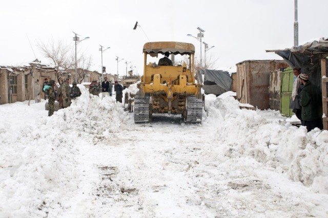 A Caterpillar D8 Bulldozer, operated by an Afghan resident, clears the road through the Shinkai Bazaar, Afghanistan, Feb. 19, 2012. The bulldozer will help clear the roads from Forward Operating Base Sweeney to the villages of Menden Kheyl and Shinkai, allowing residents from the area to reach the Shinkai Bazaar.