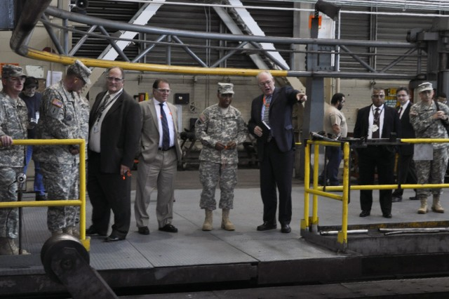 Gen. Dennis L. Via, who assumed duties as the 18th Commander of the Army Materiel Command Aug. 7, 2012, is viewed on the left of Arsenal Deputy Commander Ed McCarthy, pointing, as a 155mm tube is about to be forged.  The tube was heated to nearly 2,000 degrees.