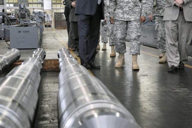 Arsenal Deputy Commander Ed McCarthy, left, briefs as Gen. Dennis L. Via walks down one of the Arsenal's production bays.