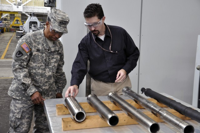 Benét Labs' Christopher Humiston briefs Gen. Dennis L. Via about the flow-form process to mortar manufacturing.  What is unique about this process is that it involves intense cold versus heat.
