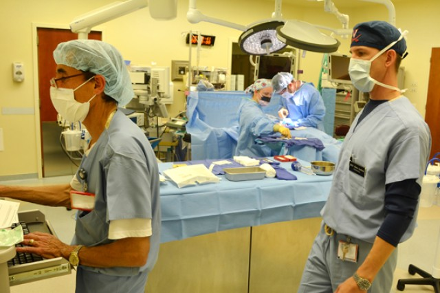Lt. Col. Eric Lewis (right), chief of anesthesia and perioperative services, watches Wilfredo Cordero, a civilian nurse, document procedures while OR technician Spc. Mikayla Cornfield and general surgeon Dr. Todd Lucas perform same-day surgery at U.S. Army Health Center Vicenza Oct. 2, 2012.