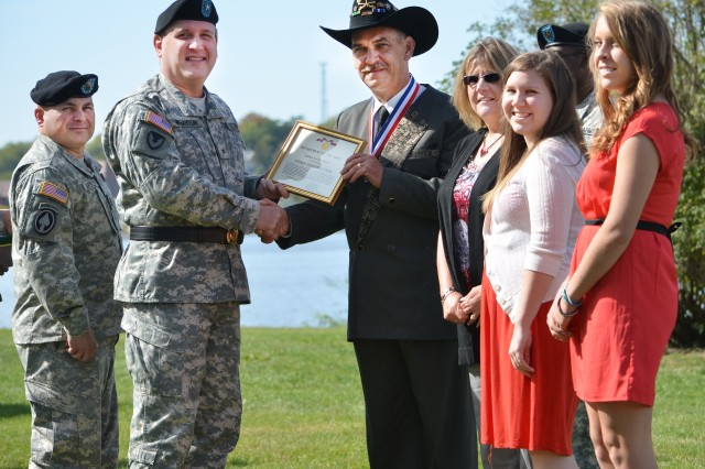 Brig. Gen. John F. Wharton, commanding general, Army Sustainment Command, presents the Superior Civilian Service Award to Robert M. Gottfreid for his 26-plus years of service during the quarterly ASC Award, Retirement & Retreat Ceremony held at historic Quarters One on Rock Island Arsenal, Sept. 27. Looking on are Gottfreid's family members and ASC Command Sgt. Maj. James E. Spencer.
