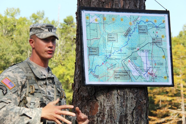 On the bank of a slough winding off the Yellow River, Army Ranger instructors took a moment Oct. 3, 2012, to remember one of the worst training accidents in the group's history. Capt. Jacob Hughes, commander, B Company, 6th Ranger Training Battalion, shows on a map the route that was taken in the events leading to the incident.