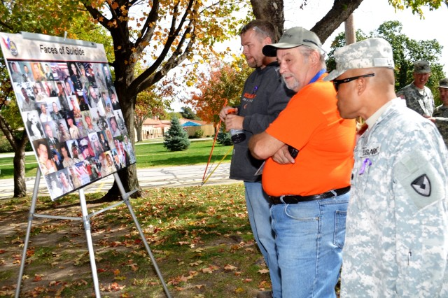 Walkers share a moment to look at a placard with photographs of suicide victims. (Photo by Galen Putnam, ASC Public Affairs)