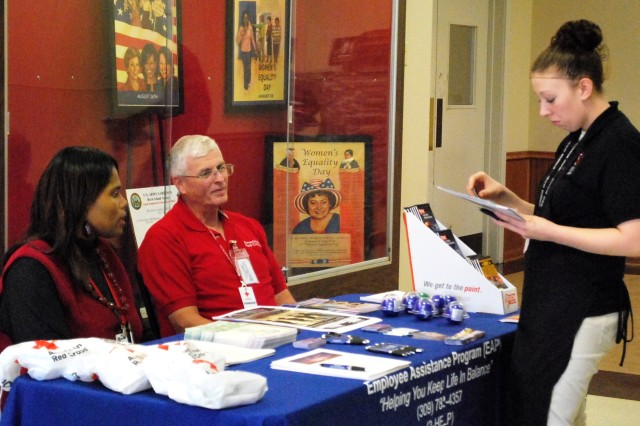 Consuela Rogers, clinical social worker, Employee Assistance Program, RIA, and Bob White, Red Cross volunteer, assist an employee by offering literature on suicide prevention. (Photo by Jon Connor, ASC Public Affairs)