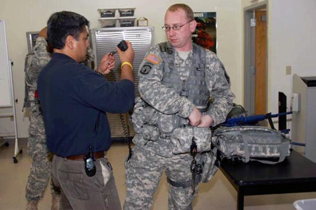Luis Illescas, an instructor with the Computer Science Corporation for the Medical Simulation Training Center (MSTC), and Sgt. Jesse Schultz of the 372nd Military Police Company of the 200th Military Police Command, Fort Meade, Md., check equipment before a training scenario. Nine members of the 200th attended the training at the MSTC at Fort McCoy.