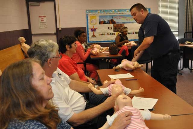 Mike Slayman, assistant chief of EMS, right, from left, Angelique Scharine, Bruce Amrein, and Mary Binseel of ARL, child care provider Brieana Lewis,  and Tanya Armstead of the APG child development center, how to perform CPR on an infant during the monthly CPR/AED class at the Post Chapel Oct. 19.