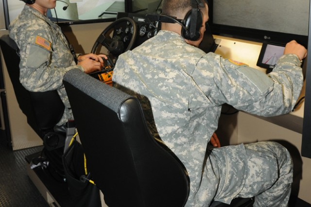 "Left, Pvt. Emmitt Kauffman and Pvt. Cristopal Reyes, both with the 235th Engineer Sapper Company from Petaluma, Calif., train on the simulated Mine Protected Clearance Vehicle or ""Buffalo"" at the Virtual Clearance Training Suite, Sept. 18, 2012, at Fort Leonard Wood, Mo."