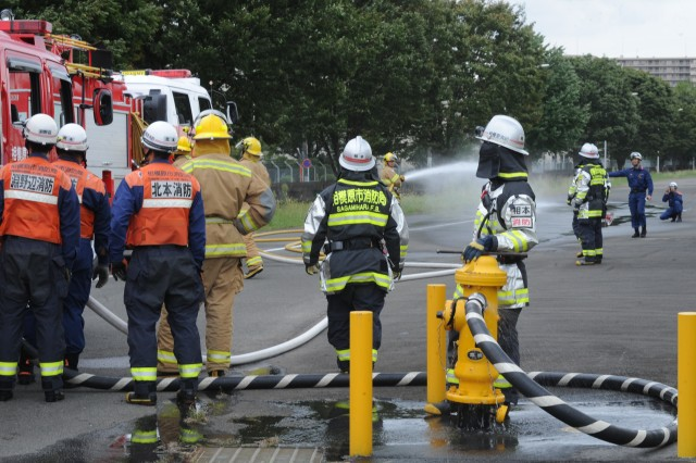 U.S. Army Garrison Japan and Sagamihara City firefighters conduct a joint hose relay exercise utilizing both organizations' fire trucks and an Army fire hydrant.