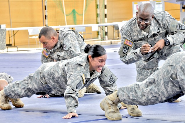 Cpl. Lisa Menela, 529th Military Police Company, gets ready for another pushup as Master Sgt. Alther Edwards counts and encourages her during a suicide prevention standdown event at the Wiesbaden Fitness Center.