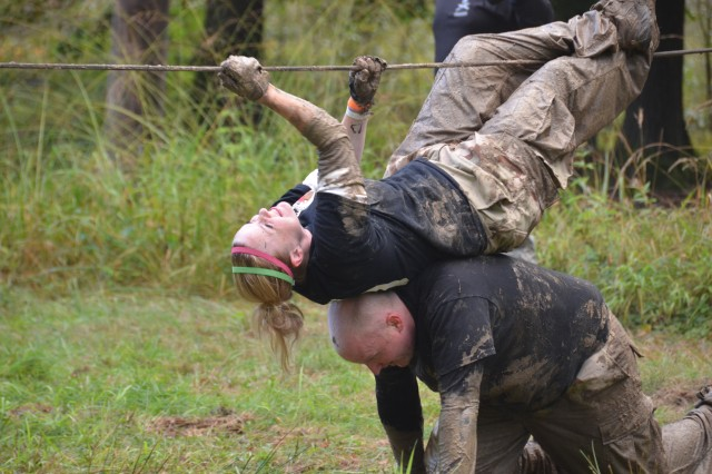 Leah Luher makes her way across the rope pull with the help of her teammate Sgt. John White during the Spartan's Race, Sept. 28, 2012, on Warner Barracks near Bamberg, Germany. Faced with 10 grueling obstacles, the team of three spouses and one Soldier completed the race and earned themselves the Team Spirit award for their strong teamwork in helping each other complete the obstacles.