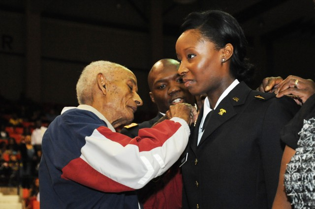 Brand new Second Lt. Jessica Webb receives her gold bars from her grandfather, World War II veteran Extra Webb. Mr. Webb also rendered his granddaughter her first salute.