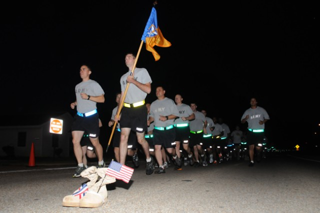 Soldiers run past one pair of the 232 sets of boots that lined the running route Sept. 27 during the Fort Rucker stand down for suicide prevention.