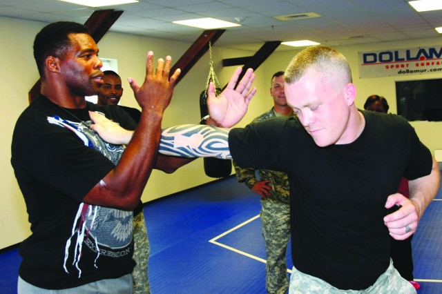 Herschel Walker, Former NFL football player and current mixed martial arts fighter demmonstrates a move on CWO3 Arron McLean, combatives instructor at the Warrior Combative Training Center, Sept. 27. Walker was at Fort Belvoir to visit with servicemembers, military affiliated employees and Families on Fort Belvoir. Walker also shared experiences during a presentation at the Community Center.