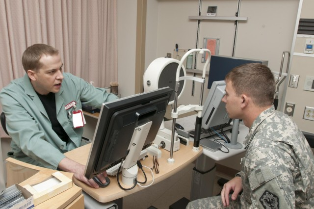 Clint Pugh, Ophthalmic technician, Laser Refractive Surgery Center, Madigan Healthcare System explains the procedure for the corneal scan to 1st Lt. Christopher Griggs, executive officer, 14th Engineer Battalion, 555th Engineer Brigade, as part of the process to determine if he is a candidate to have the Photorefractive Keratectomy (PRK) or Laser-Assisted in Situ Keratomileusis (LASIK) procedure done on his eyes.The procedures are provided free of charge to active duty service members who meet specific criteria, as part of the Warfighter Refractive Eye Surgery Program developed by the Department of Defense. The program provides the procedures to boost mission readiness.