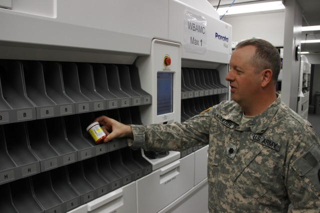 Lt. Col. Mark Krueger, chief of pharmacy at WBAMC, demonstrate the automated medication dispensing system used in the outpatient pharmacy.