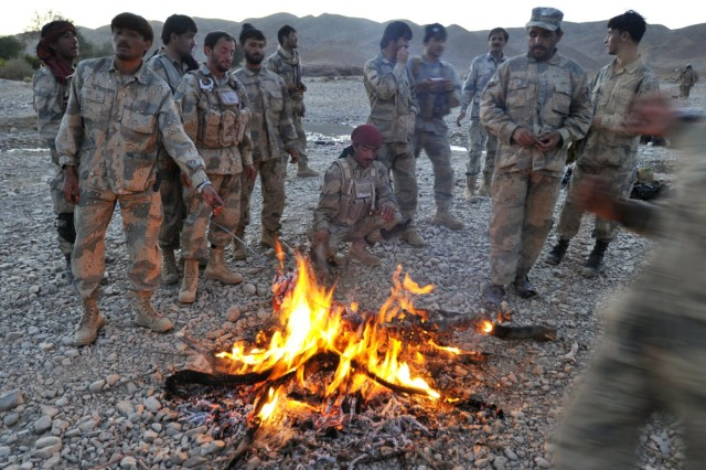 Members of the 3rd Zone Afghan Border Police wait for their dinner to cook after a mission during Operation Southern Fist in Afghanistan's Spin Boldak district, Sept. 29, 2012. The Afghan-led operation focused on denying the enemy freedom of maneuver and to connect local villagers with the Afghan government.