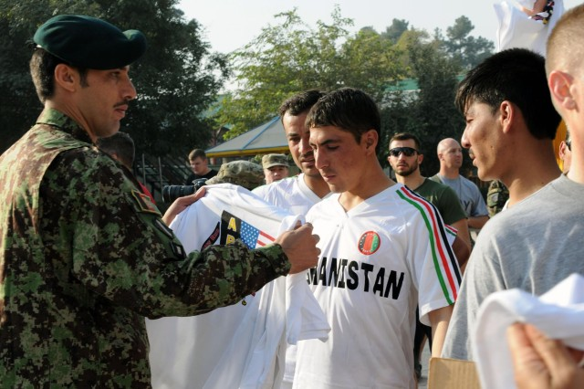 Afghan National Army Command Sgt. Maj. Muhebullah, the senior noncommissioned officer of the ANA's Army Support Command, hands out t-shirts to his soldiers who were invited to participate in the Army Ten-miler shadow run at Camp Eggers, Kabul, Afghanistan, Oct. 7, 2012. Some of the ANA soldiers came from outlying areas and were selected by their units to represent them for the event. Six of the seven invitees conducted the run in less than 78 minutes. The ANA was invited by their logistics mentors and trainers to participate in the run, as a team building even of sorts.