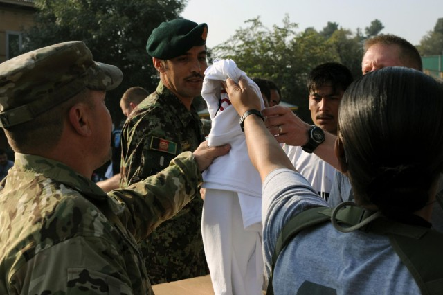 Organizers hand out T-shirts upon completion of the Camp Eggers Army Ten-Miler shadow run, Oct. 7, 2012. More than 200 participants signed up at this particular location, to include Afghan National Army soldiers who were invited to the event by their Deputy Command of Support Operations logistics mentor and trainer counterparts.