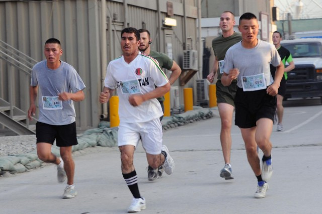 Afghan National Army soldier, Monir Khan (center), a medic from Regional Logistics Support Command-East runs side by side with U.S. Marine Corps, Mongolian and other coalition forces participants of the Oct. 7, 2012, Camp Eggers Army Ten-Miler shadow run. Khan said his unit's rigorous physical fitness program prepared him for the competition.