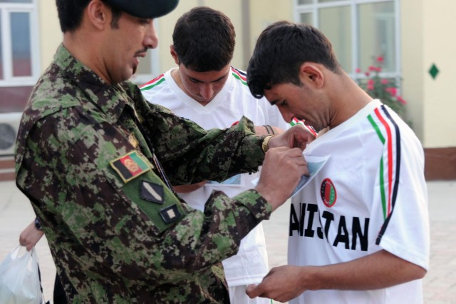 Afghan National Army Command Sgt. Maj. Muhebullah, the senior noncommissioned officer of the ANA's Army Support Command, pins a bib on one of his soldiers, Oct. 7, 2012, minutes before the Camp Eggers, Afghanistan, Army Ten-Miler shadow run. Some logistics trainers and mentors from the Deputy Command of Support Operations, NATO Training Mission-Afghanistan, invited the ANA soldiers to participate in the run.