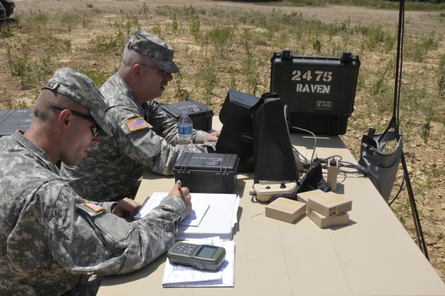 Staff Sgt. Jeremy Phetteplace of Manhattan, Kan., left, records the flight log of a Raven's test flight July 25 at Fort Chaffee, Ark as Sgt. Brian Randolph of Wichita, Kan,, plots the grid points on a Panasonic Toughbox laptop for the Raven. Both are members of the Army Reserve 346th Military Police Company of Fort Riley, Kan.
