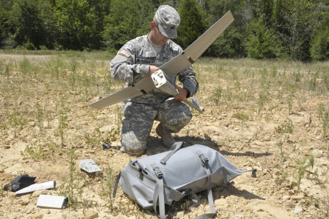 Staff Sgt. Jeremy Phetteplace of Manhattan, Kan., and a member of the Army Reserve 346th Military Police Company of Fort Riley, Kan. assembles a Raven B Small Unmanned Aerial Vehicle before a test flight July 25 at Fort Chaffee, Ark. A Raven has a wing span of almost five feet and weighs a little more than four pounds. It fits in the tactical bag in front of Phetteplace.