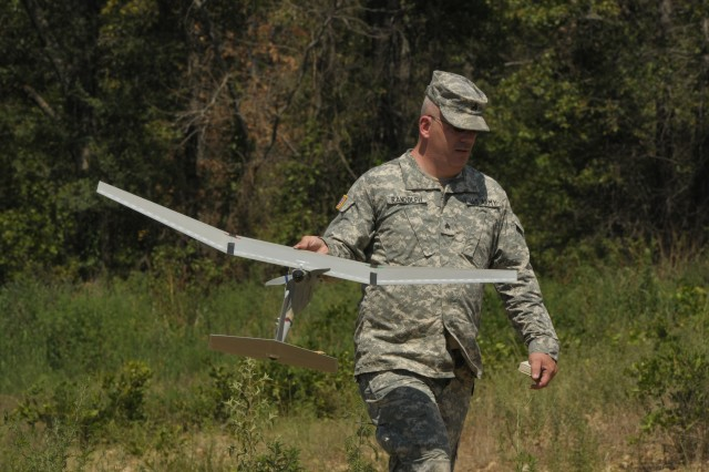 Sgt. Brian Randolph of Wichita, Kan., and a member of the Army Reserve 346th Military Police Company of Fort Riley, Kan., brings back a Raven B Small Unmanned Aerial Vehicle after a test flight July 25 in Fort Chaffee, Ark. The fuselage and payload or nose of the plane are the only two items that must be recovered in case of a crash.