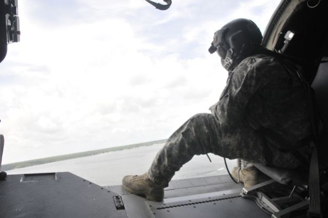 Sgt. Mike Pelegrin, a crew chief for the Florida Army National Guard's Company C, 1st Battalion, 111th Aviation, watches as a HH-60M Black Hawk makes a banking move as it flies over a lake on Camp Blanding, Fla., July 20, 2012, during a joint National Guard and Army Reserve medevac operation.