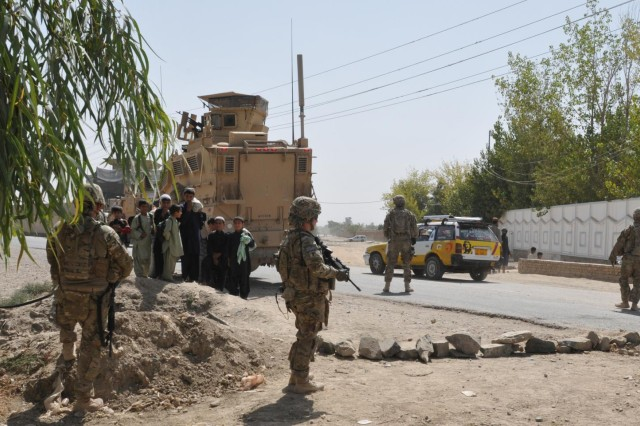 Soldiers from the 563rd Military Police Company, currently deployed to southern Afghanistan as part of Combined Task Force Lancer, 2nd Stryker Brigade Combat Team; a narcotics patrol detector dog handler with the 3rd Infantry Division and Afghan Uniform Police members conduct a traffic control point during Operation Clean Sweep in Kandahar City, Oct. 3, 2012.