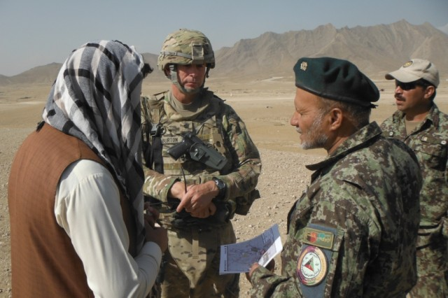 Lt. Col. Robert Burton, First Army Division East Trainer Mentor Team-East commander, along with a members of the Afghan National Army, speak to a local national during the TMT transition.
