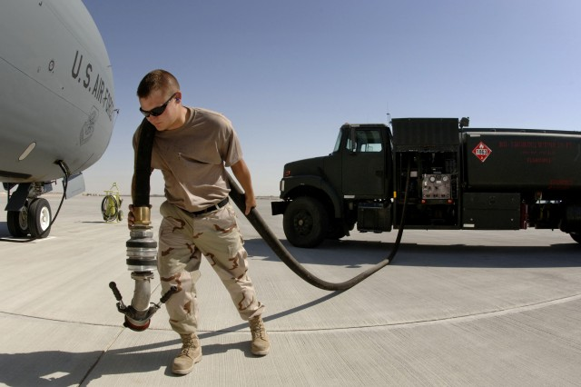 Air Force Airmen Mark Heitkamp pulls a fuel service hose from an R-11 fuel truck in preparation for refueling a KC-135 Stratotanker aircraft with JP-8 fuel at an air base in Southwest Asia, May 31, 2006.