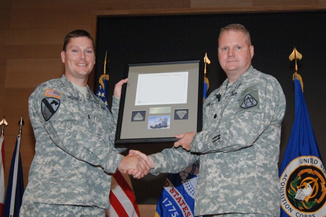 Lt. Col. Greg Coile, product manager for Warfighter Information Network-Tactical Increment 1, (right) handed off the last piece of WIN-T Increment 1 equipment to the receiving unit during the Final Fielding Celebration of WIN-T Increment 1, Aug. 23, 2012.