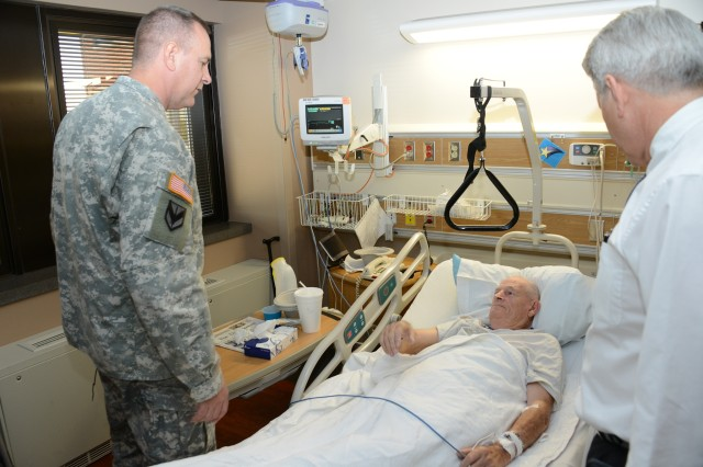Brig. Gen. Kevin G. O'Connell, commander, Joint Munitions Command, and Barry Sharp, director, Iowa City VA Medical Center, visits World War II veteran and Cedar Rapids-native Max Hocken, during a Sept. 27 visit by the general to the medical center.