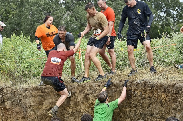 """AUSTIN, Texas - Command Sgt. Maj. Mervyn Ripley, command sergeant major of 1st """"Ironhorse"""" Brigade Combat Team, 1st Cavalry Division, receives help out of an obstacle from staff members of 1BCT during the Austin, Texas 2012 Tough Mudder. Ripley said this is his third time participating in a Tough Mudder and he enjoys the challenge."""
