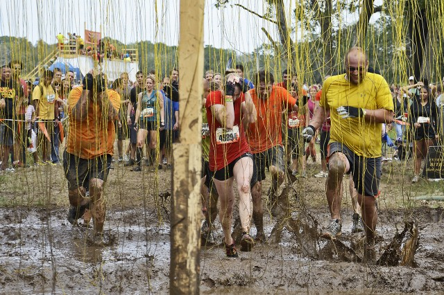 """AUSTIN, Texas - Participants in the Austin, Texas 2012 Tough Mudder run through the final obstacle of the race known as """"Electroshock Therapy,"""" Oct. 6. Only a few random yellow strings were charged with electricity. Several members of the 1st Cavalry Division participated in the Tough Mudder."""