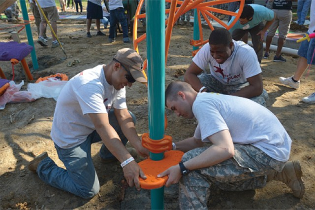 Volunteers place steps on a piece of equipment on the new playground. More than 525 volunteers gathered Oct. 6 to build a playground in Monroe Manor on Fort Lee with the help of the Villages at Fort Lee, KABOOM! and Dr. Pepper Snapple Group.